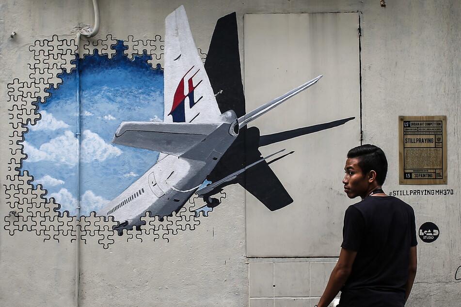 Ein Mann steht vor einem Wandgemälde, auf dem das Verschwinden des Malaysia-Airlines-Flugs MH370 dargestellt ist.