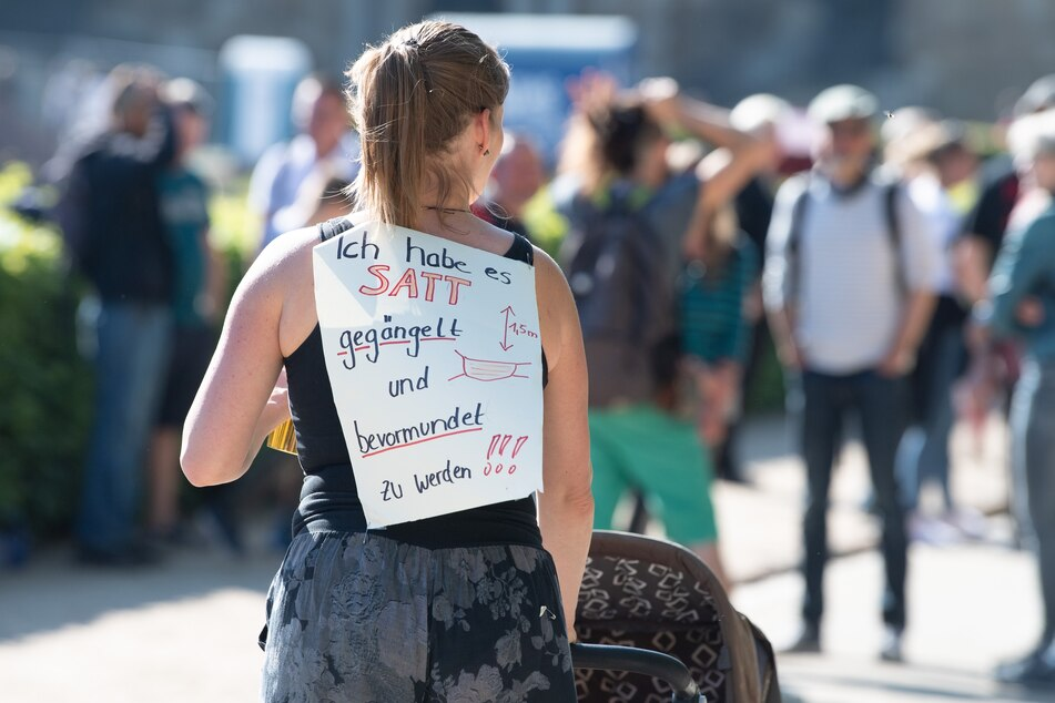 """Eine Teilnehmerin einer Kundgebung von Anhängern von Verschwörungstheorien zur Corona-Krise trägt am 16. Mai im Großen Garten in Dresden ein Schild mit der Aufschrift """"Ich habe es satt gegängelt und bevormundet zu werden""""."""