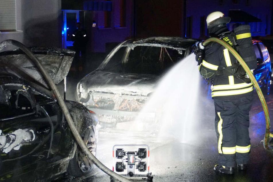 Feuerwehrmann löscht eines der brennenden Autos.