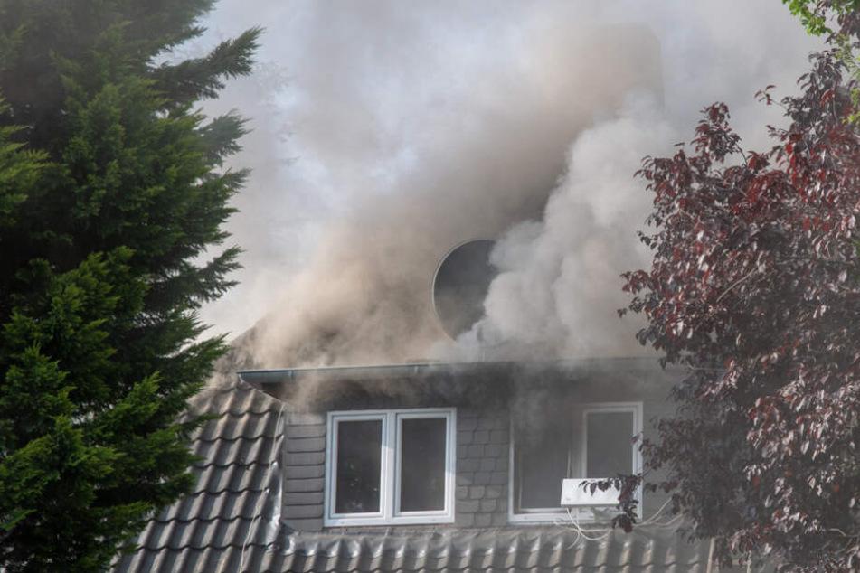 Dichter Qualm steigt aus dem Dach eines Hauses in Hamburg auf.
