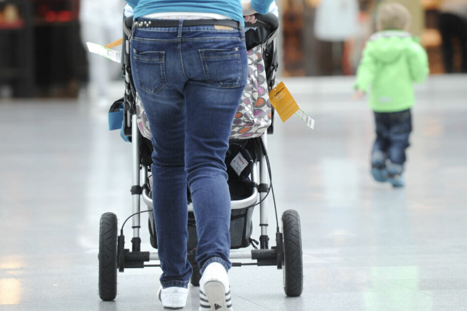 Eine Mutter geht mit einem Kinderwagen einen Weg entlang. (Symbolbild)
