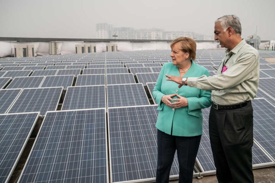 Angela Merkel besichtigt die mit Solarenergie betriebene Metrostation Dwarka Sector 21 und lässt sich im Rahmen des Besuchs den Betrieb von elektrisch angetriebenen e-Rikschas erklären.