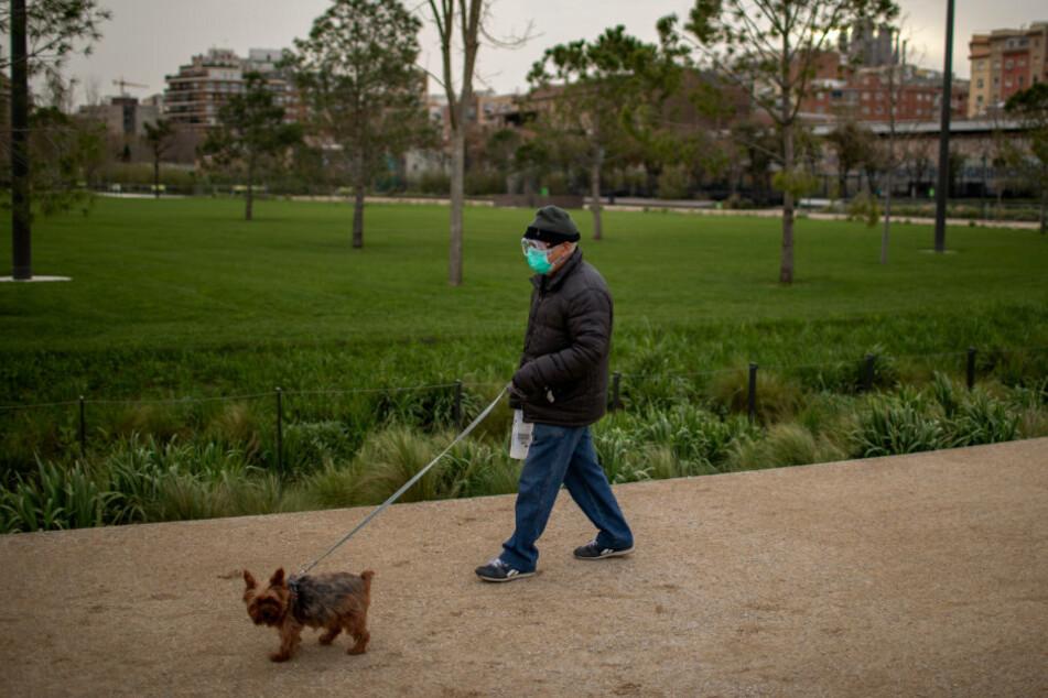 Spanien, Barcelona: Ein Mann mit Mundschutz und Schutzbrille geht mit seinem Hund spazieren.