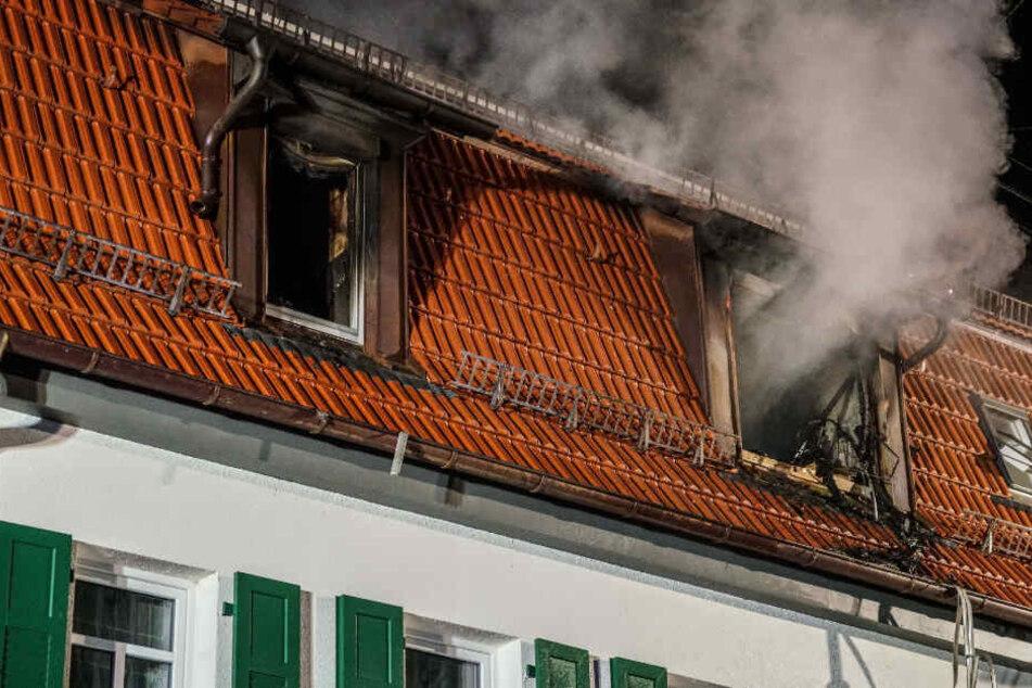 Rauch steigt aus zwei Fenstern einer Asylunterkunft auf.