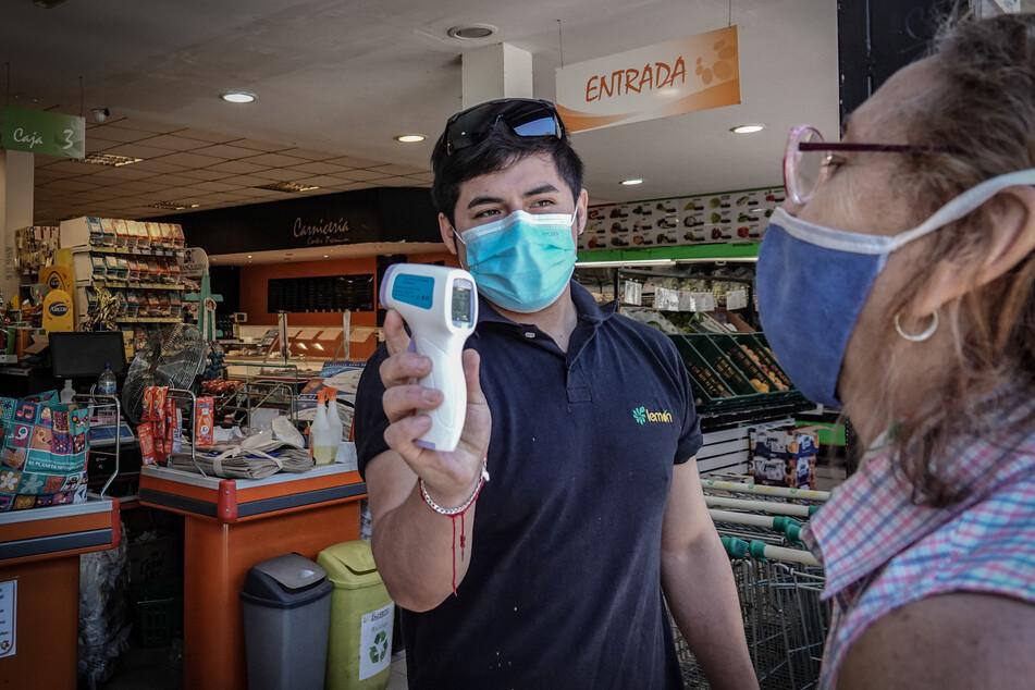 Eine Frau lässt ihre Temperatur messen, bevor sie einen Supermarkt betritt.