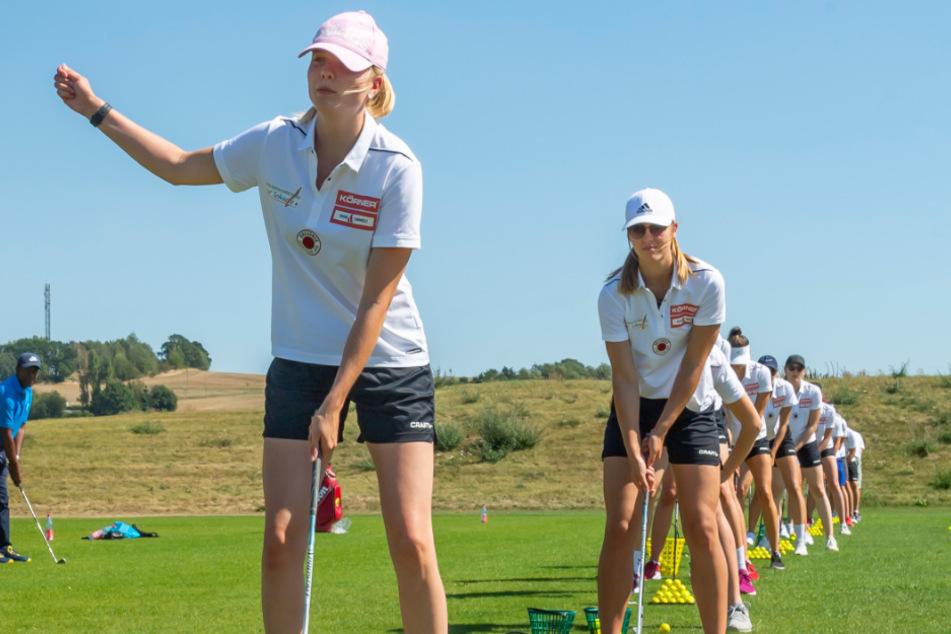 Die DSC-Volleyballerinnen stehen auf dem Golfplatz in einer Reihe, um den Abschlag zu üben - vorn Jennifer Janiska.