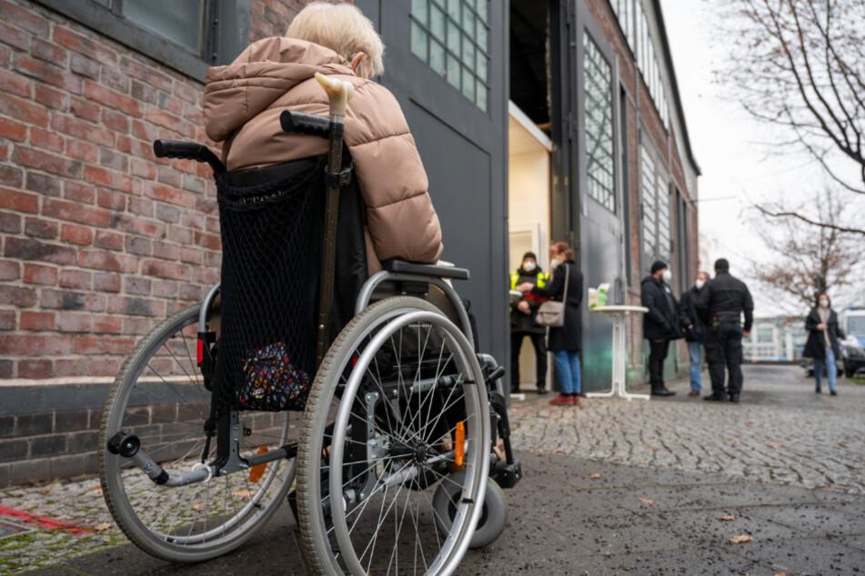 Eine Frau im Rollstuhl wartet vor dem Impfzentrum in der Treptow Arena auf die Impfung gegen das Coronavirus.