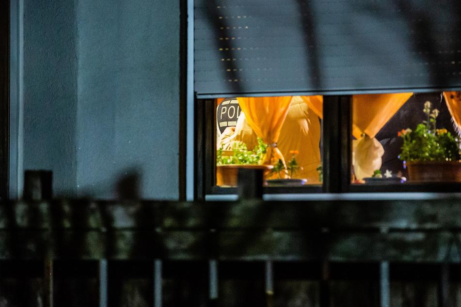 Durchs Fenster kann man einen Polizeibeamten erblicken, der sich in der gestürmten Wohnung aufhält.