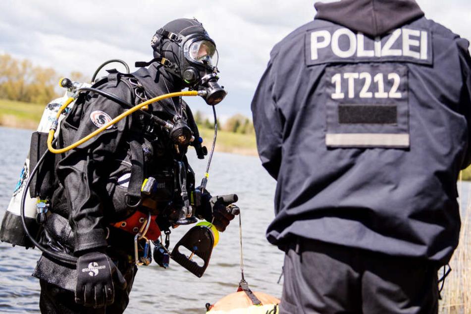 Polizeitaucher bereiten sich an einem See auf ihren Such-Einsatz vor. (Symbolbild)