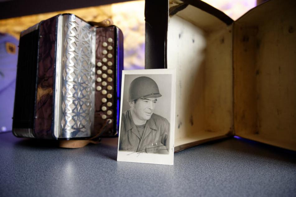Ein Foto des Amerikanischen Soldaten Andrew Kindsvater lehnt an einem Akkordeon.