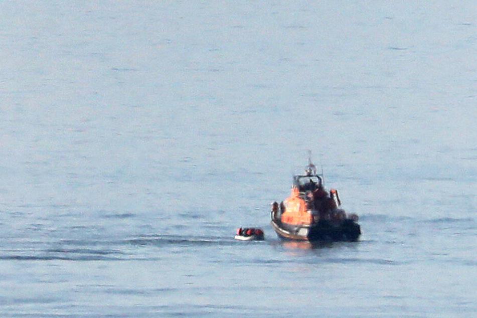 Ein Rettungsboot (r) nähert sich einem kleinen Boot, von dem angenommen wird, dass es Migranten befördert.