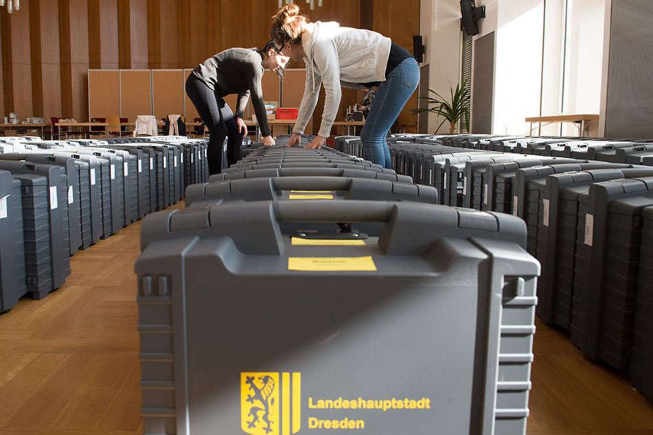 Zwei Stadt-Mitarbeiterinnen bereiten im Dresdner Rathaus die Wahlkoffer mit den Stimmzetteln vor.