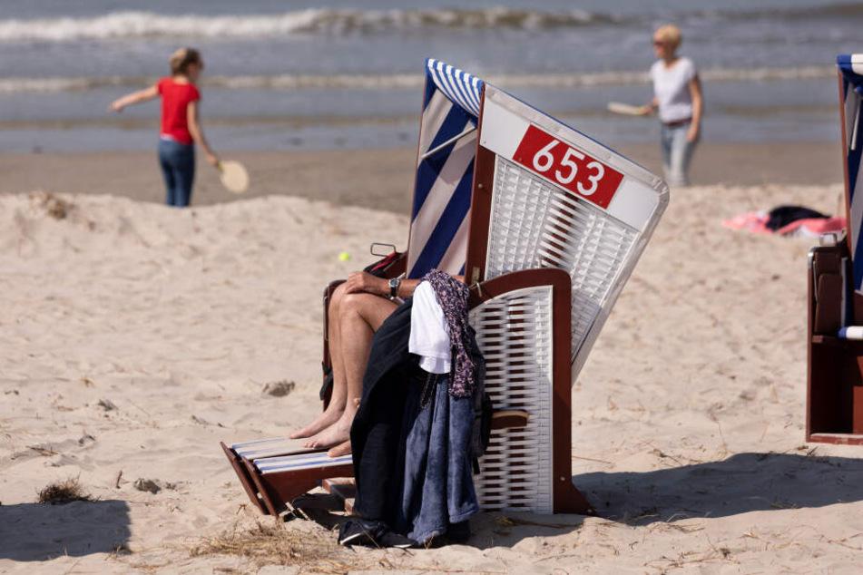 Urlauber sitzen Mitte April in einem Strandkorb auf Norderney.