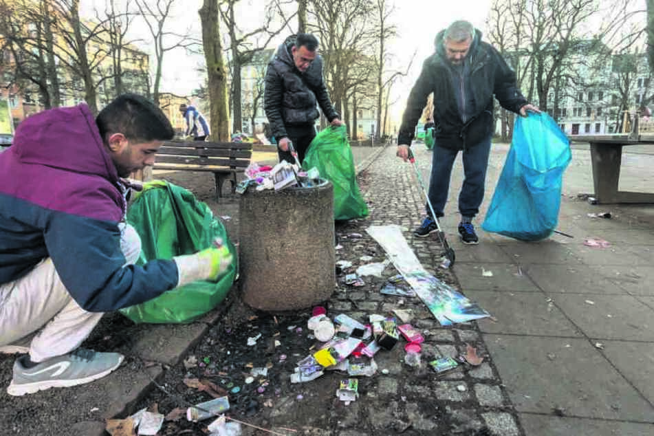 Sadegh (30), Mohamad (50) und Thomas (v.l.) räumten die Feuerwerksreste auf dem Lessingplatz weg.