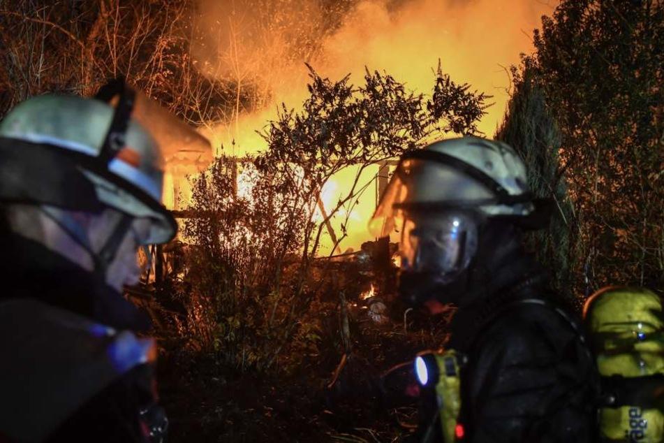 Zwei Feuerwehrleute stehen vor der brennenden Gartenlaube.