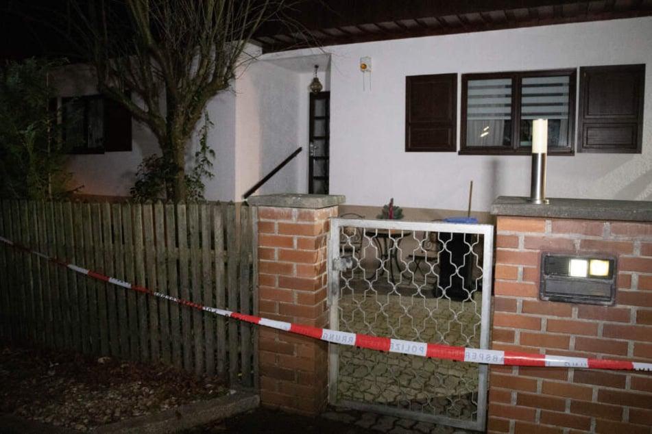 Ein Absperrband der Polizei ist vor dem Haus, in dem drei Tote entdeckt wurden, angebracht.