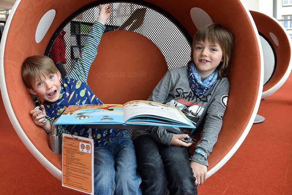 Leo (6, li.) und Toni (9) lümmeln vergnügt in einem Audiosessel. 2017 wurden bei den Städtischen Bibliotheken Dresden insgesamt knapp 970.000 Kinderbücher ausgeliehen.
