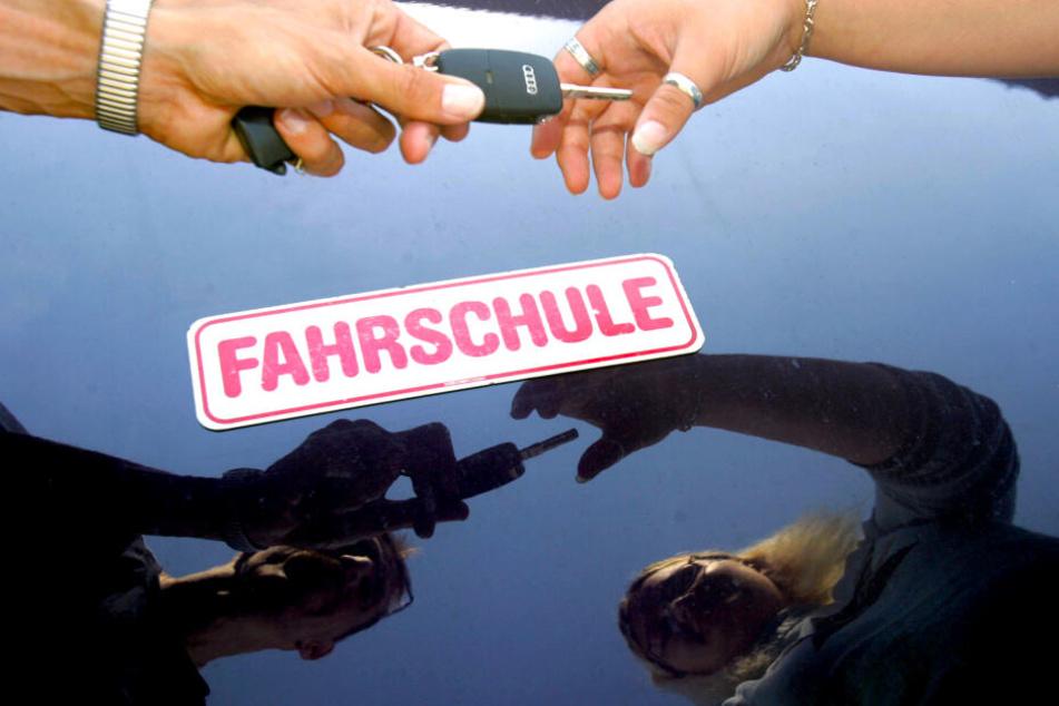 Ein Fahrlehrer überreicht seiner Fahrschülerin den Schlüssel zum Fahrzeug. Junge Menschen in Deutschlands Ballungsgebieten haben es mit dem Führerschein allerdings immer seltener eilig.
