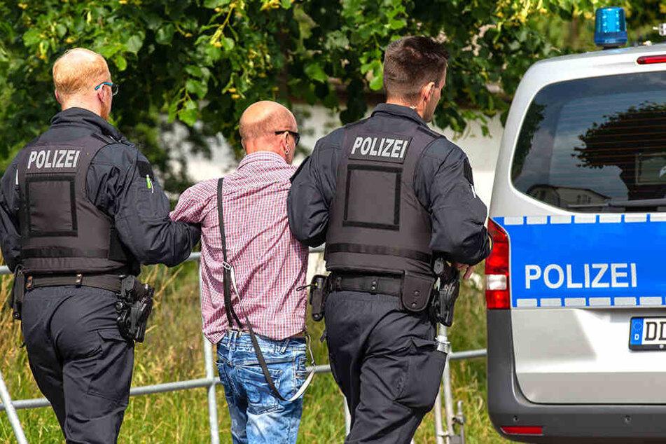 """Ein Teilnehmer des """"Schild und Schwert""""-Festivals wird nach einer Attacke auf Journalisten abgeführt."""