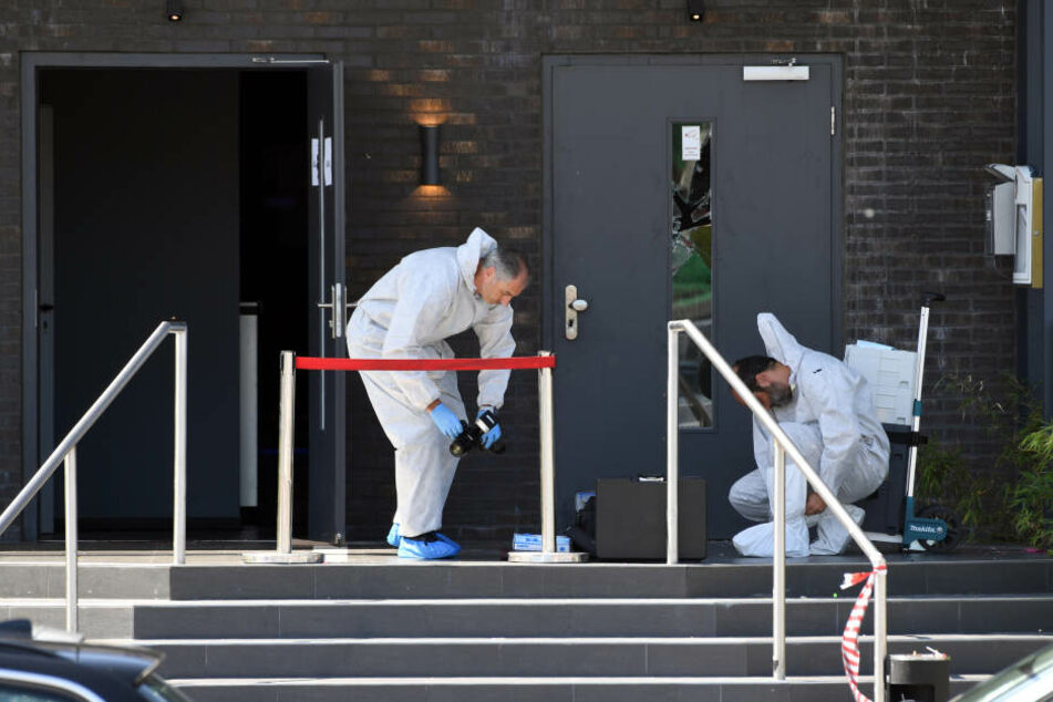 Zwei Polizisten in weißen Schutzanzügen nehmen die Spurensicherung vor dem Club Grey auf.
