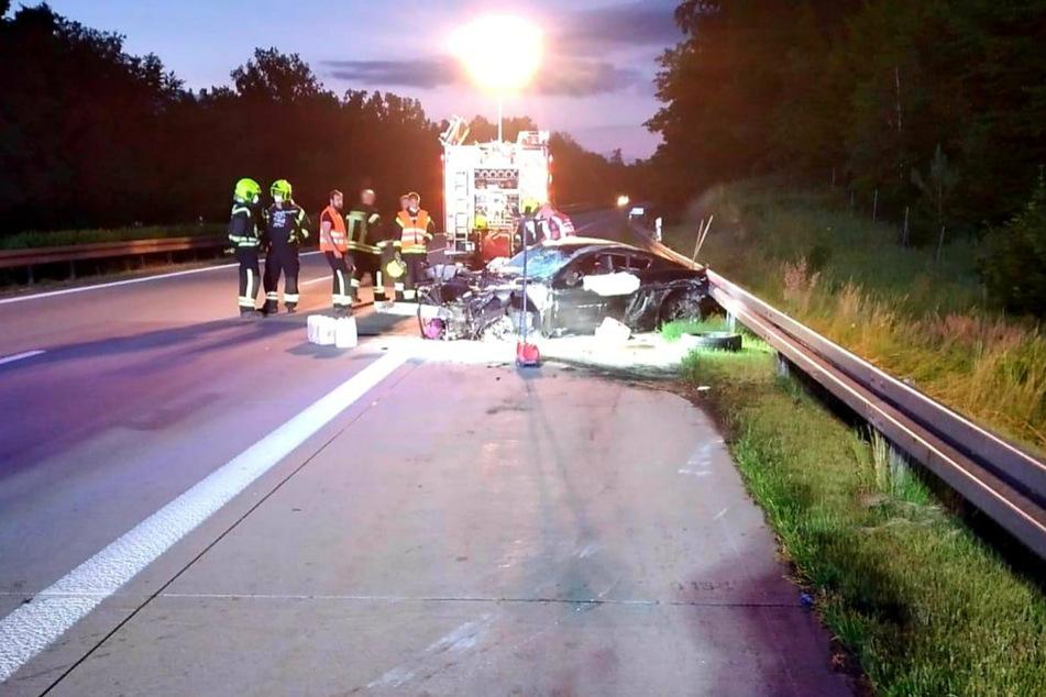 Einsatzkräfte begutachten das Unfallwrack auf der A11.