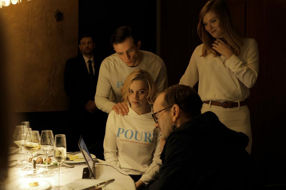 """Luna Wedler (21) als Maxi, Jannis Niewöhner (29, l.) als Karl, Fleur Geffrier (35, r.) als Odile Leconte und Milan Peschel (53, vorn) als Alex in einer Szene des Films """"Je suis Karl""""."""