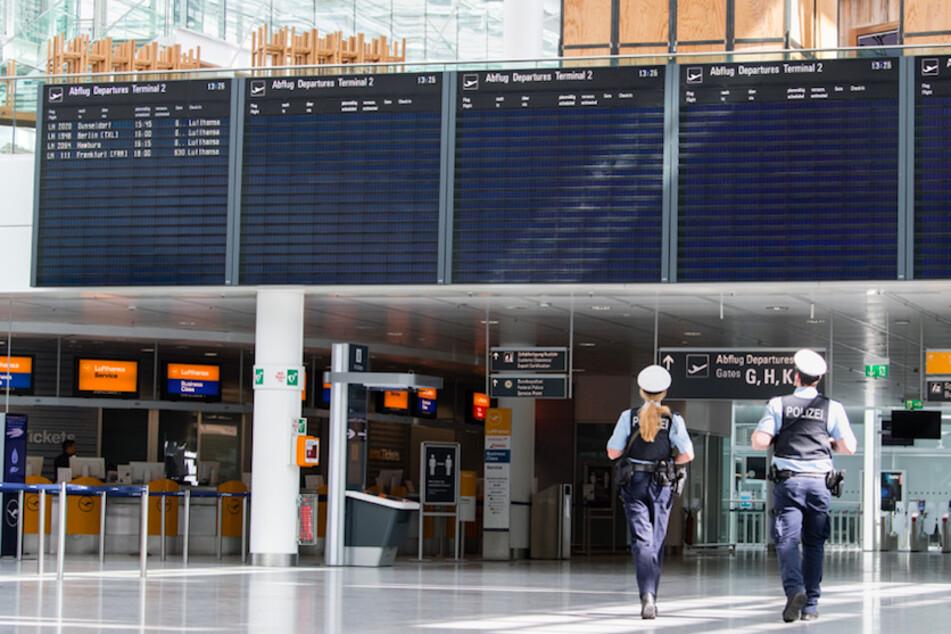 Zwei Polizisten gehen durch das ansonsten fast menschenleere Terminal vom Flughafen München.