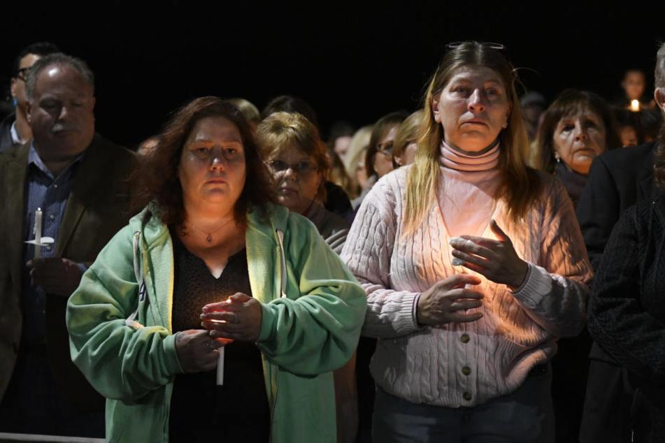 Maria Busch (l) und Tammy Smith nehmen mit anderen Angehörigen an einer Gedenkveranstaltung teil und halten Kerzen.