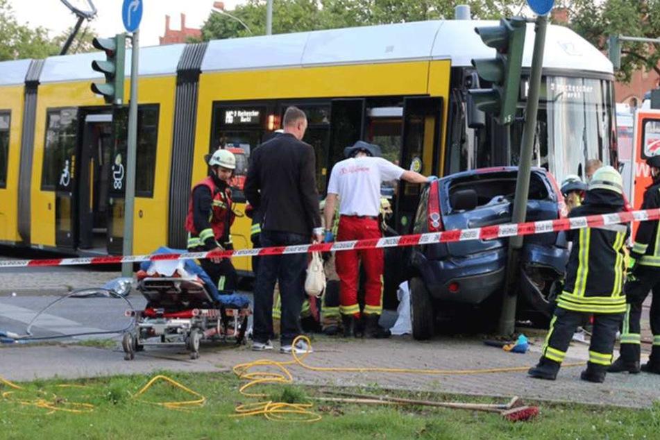 Rettungskräfte sind damit beschäftigt, die Verletzten aus dem Auto zu bergen.