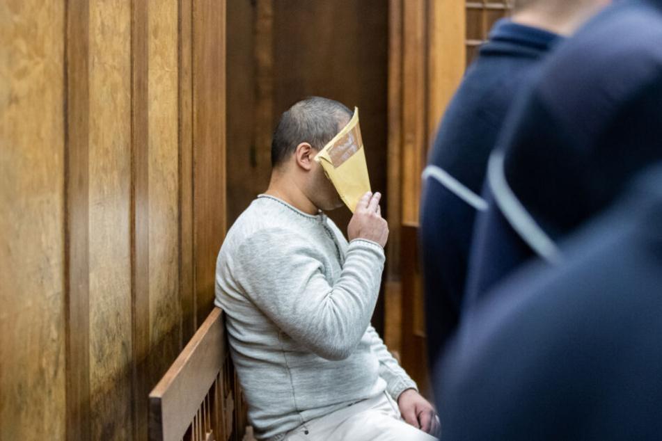 Der Angeklagte sitzt zu Beginn seines Prozesses mit einem Briefumschlag vor dem Gesicht im Landgericht im Gerichtssaal.