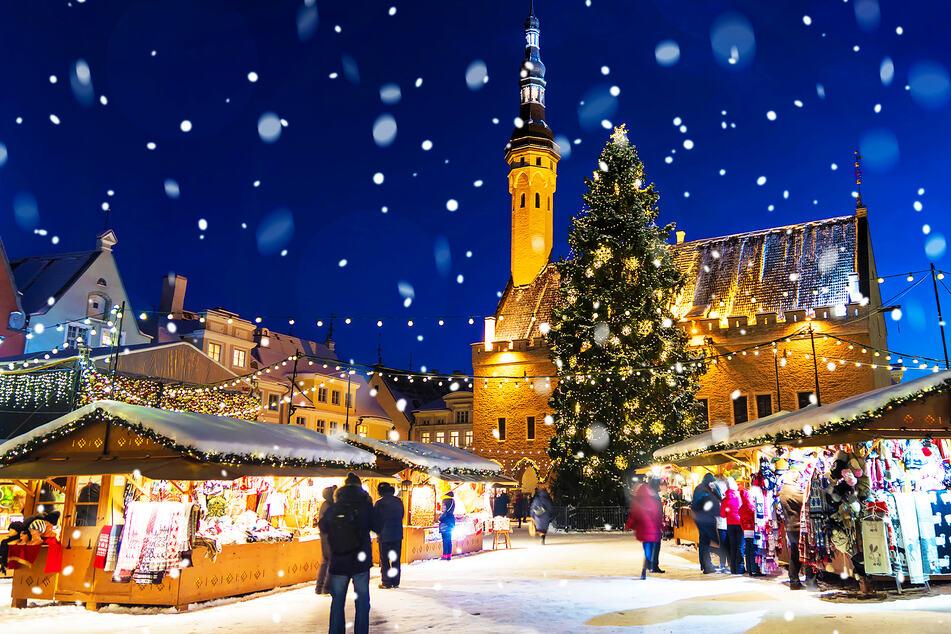 Blick auf einen Weihnachtsmarkt während Schnee fällt (Symbolbild).