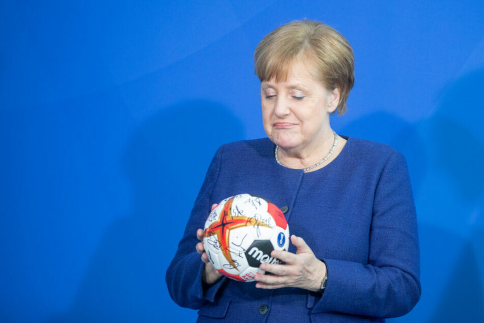 Bundeskanzlerin Angela Merkel schaut sich den unterschriebenen Handball der deutschen Nationalmannschaft an.