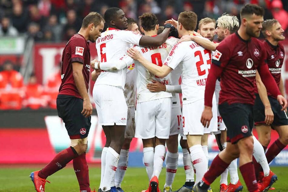 Die Spieler von RB Leipzig bejubeln das 1:0, während Nürnbergs Kicker niedergeschlagen zu Boden gucken.