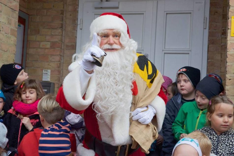 Der Weihnachtsmann überreicht seine Geschenke an Kinder.