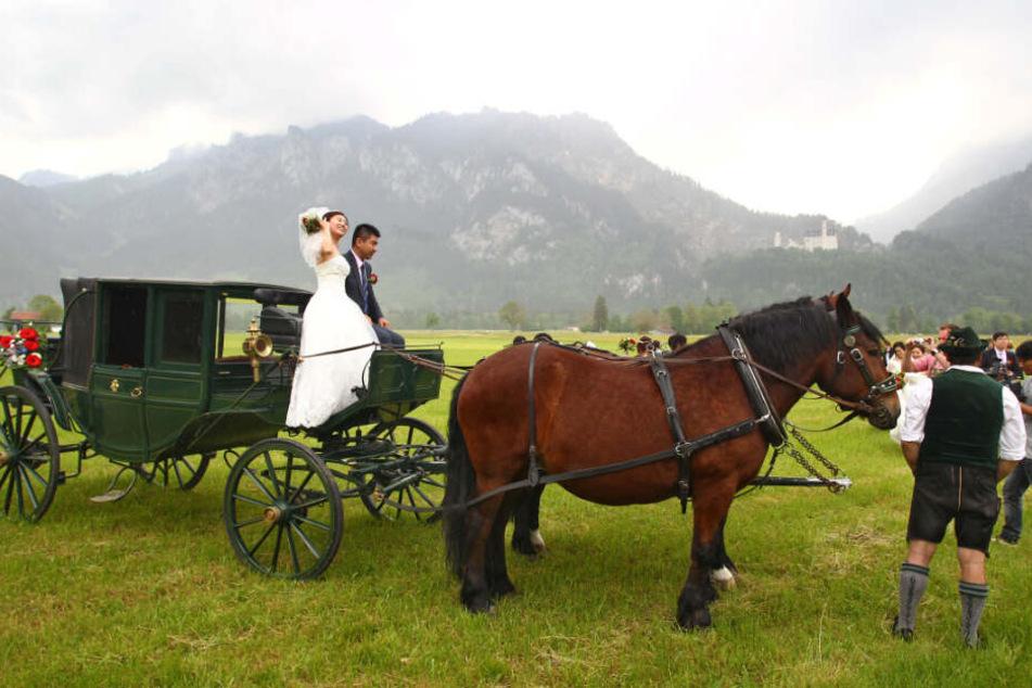 Ein chinesisches Brautpaar posiert vor dem Schloss Neuschwanstein. (Symbolbild)