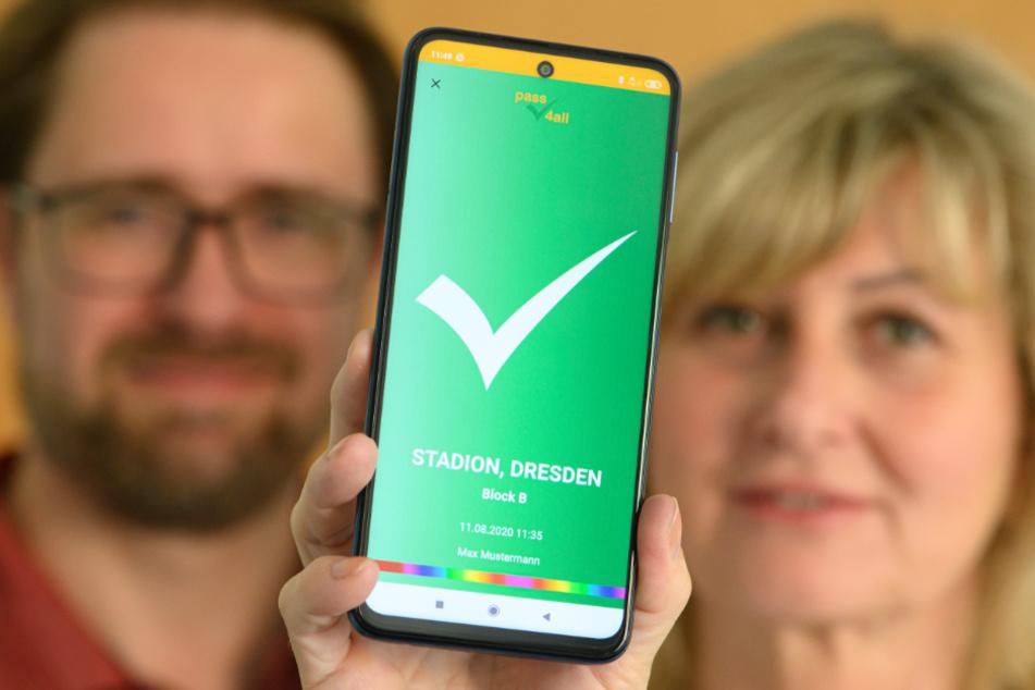 """Dresden: Kathleen Parma und Jörg Meißner, Entwickler vom sächsischen Startup """"pass4all"""", halten ein Smartphone mit der App-basierten Lösung zur anonymen Kontaktnachverfolgung mit verifizierten Kontaktdaten in den Händen."""