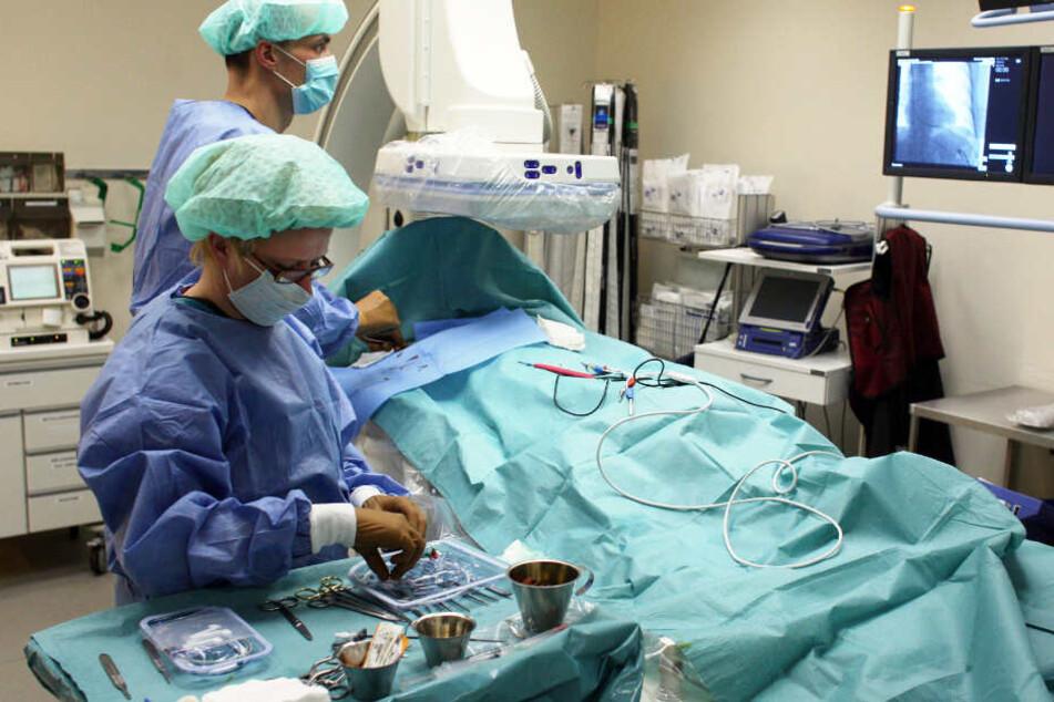 Zwei Ärzte setzen während einer OP einen Herzschrittmacher ein.