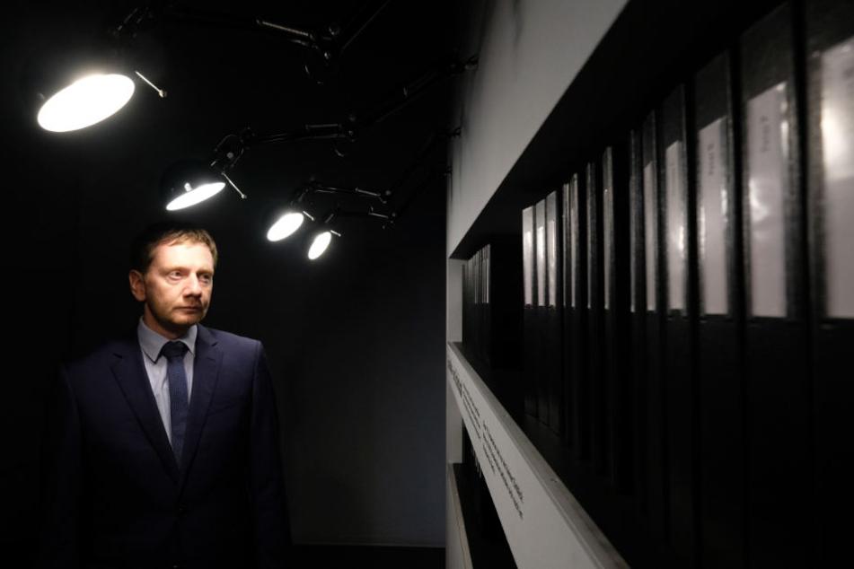 Der sächsische Ministerpräsident Michael Kretschmer (CDU) betrachtet in der Gedenkstätte Geschlossener Jugendwerkhof Torgau ausgestellte Insassen-Dokumente. Er besuchte den Ort im Rahmen seines Aufenthaltes während des 27. Tag der Sachsen.