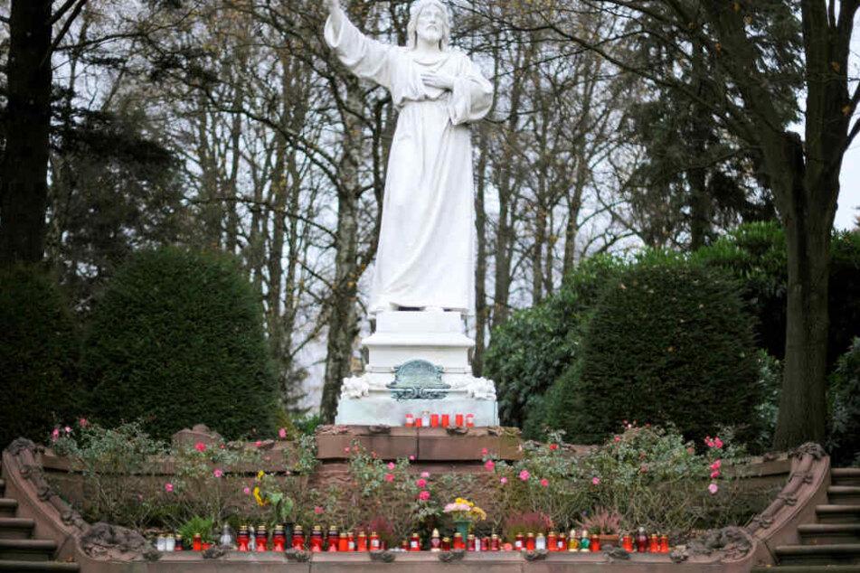 Vor einer Christusstatue auf dem Friedhof Ohlsdorf stehen zahlreiche Kerzen. Der Besuch mit dem Auto soll bald Eintritt kosten.