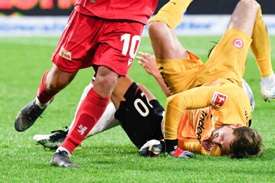 Das Foto zeigt den Moment der Verletzung: Kevin Trapp (r), Makoto Hasebe (hinten) und Sebastian Andersson von Union Berlin waren in einem Zweikampf aufeinander geprallt.