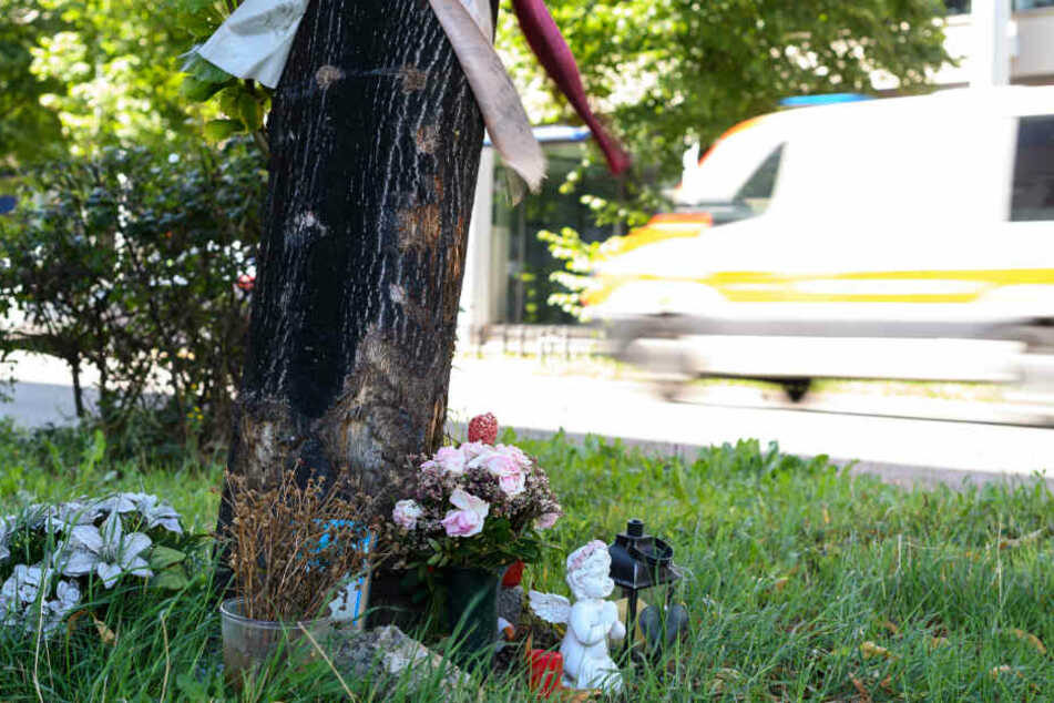 Blumen sind an einem Baum an der Unfallstelle niedergelegt.