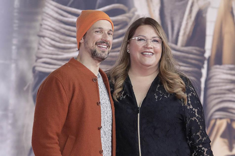 Die Schauspieler Florian David Fitz und Ilka Bessin lächeln in die Kameras.