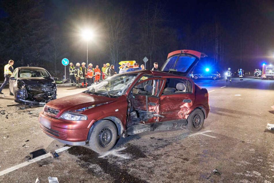 Helfer stehen neben den zwei beschädigten Autos auf einer Kreuzung.