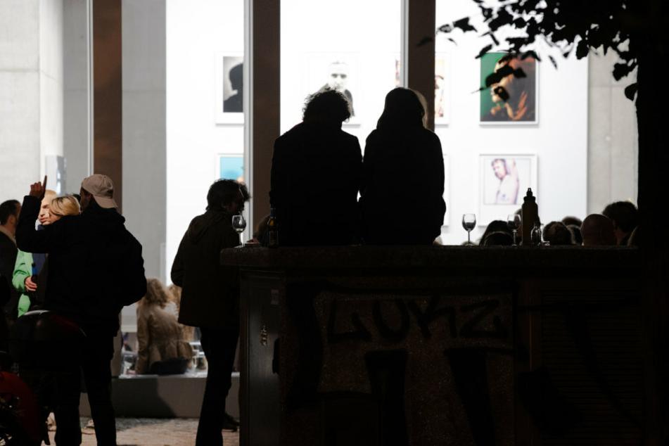 Menschen sitzen am Abend vor einer Galerie in Berlin.