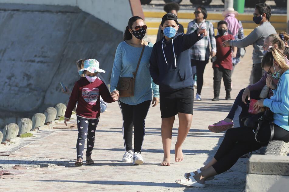 Familien spazieren am Strand von Muizenberg in Kapstadt. Ein Viertel der in Afrika gemeldeten Fälle entfällt auf Südafrika, gefolgt von Ägypten, Nigeria und Ghana.