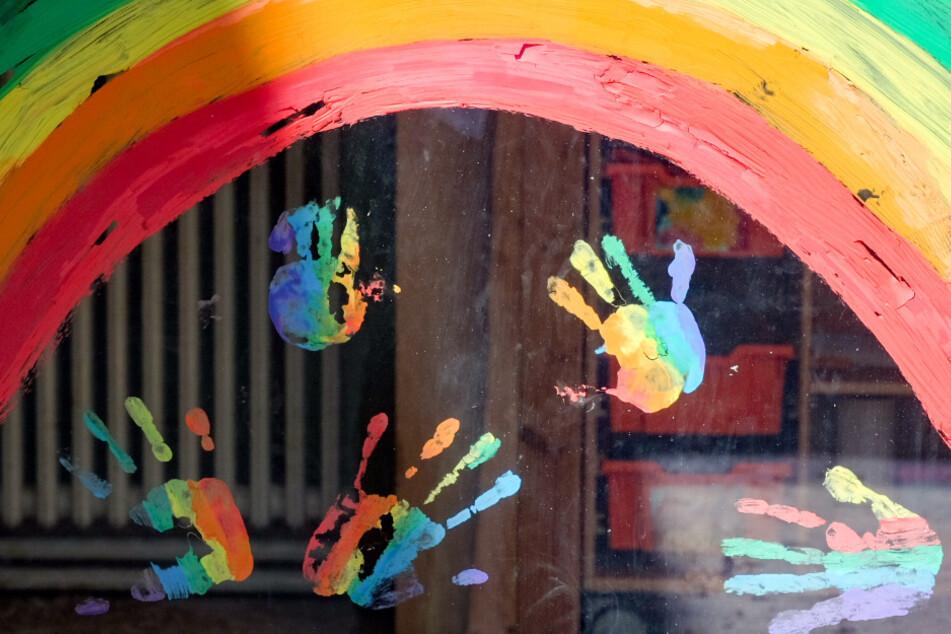Kinderhände und ein Regenbogen sind an einer Kita zu sehen.
