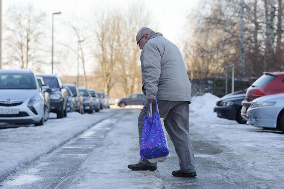 Vorsichtig läuft ein Mann über die völlig vereiste Kutusowstraße.