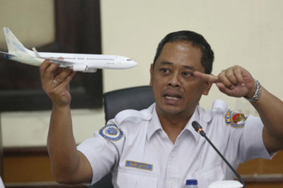 Ein Ermittler des Nationalen Verkehrssicherheitskomitees am Modell eines Flugzeugs was passiert sein könnte.