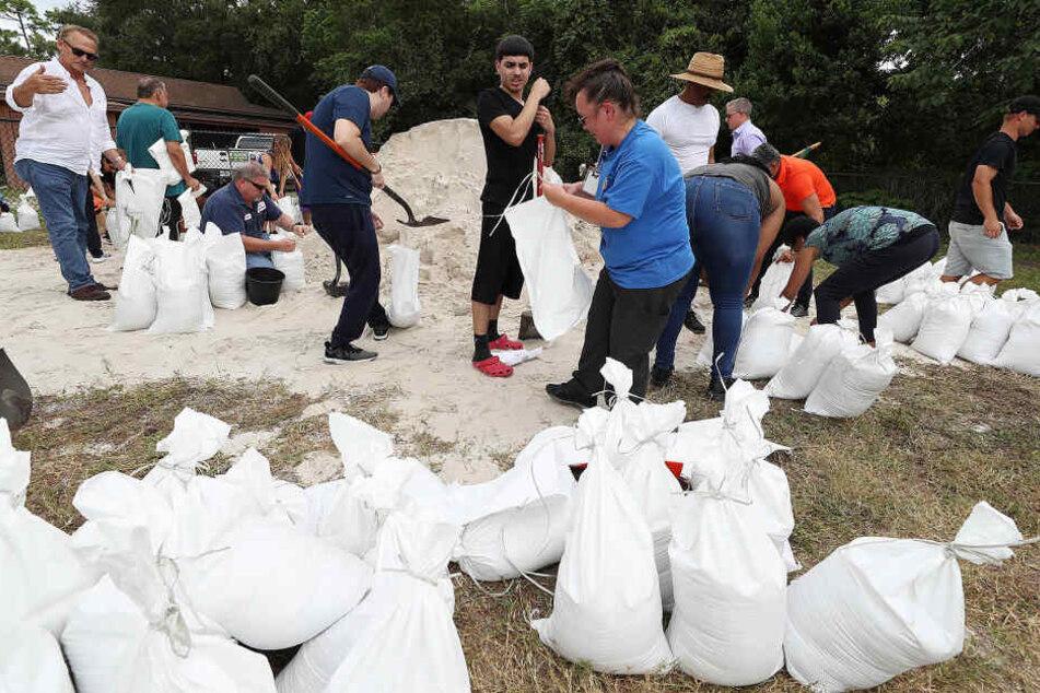 """Bewohnern füllen Sandsäcke im Blanchard Park. Wegen des herannahenden Hurrikans """"Dorian"""" hat der Gouverneur des US-Bundesstaates Florida den Notstand ausgerufen."""