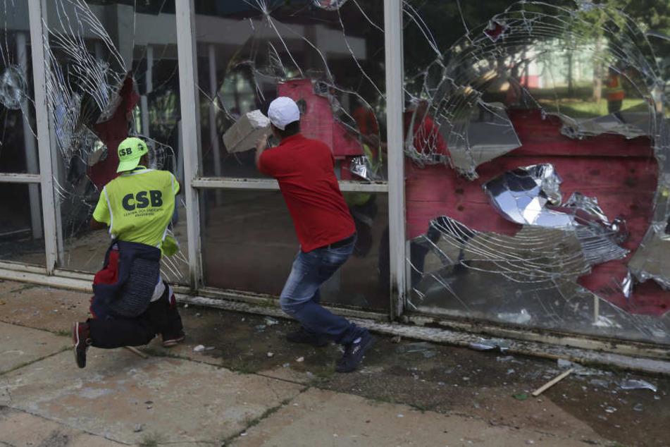 Demonstranten schlagen während der heftigen Proteste die Fensterscheiben des Ministeriums für Wissenschaft, Technologie und Innovation ein.